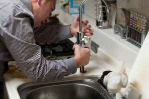 A plumber fixing the kitchen sink pipe.
