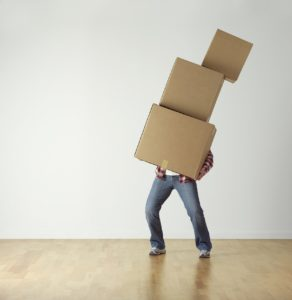 A person carrying three large boxes