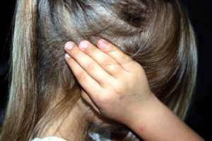 A child covering her ears.